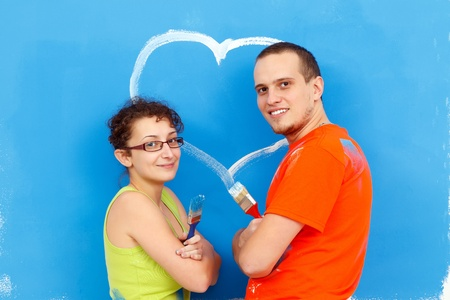 Young couple with a heart painted on the wall photo