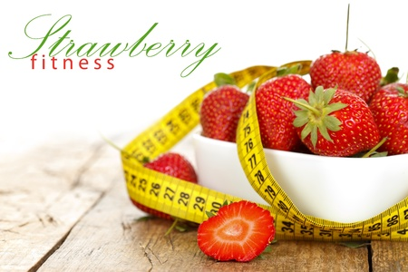 Closeup of a bowl with strawberries and a measure tape with place for your text on the left Stock Photo