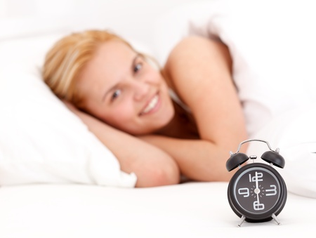 Alarm clock with a young woman lying in the bed at the background photo