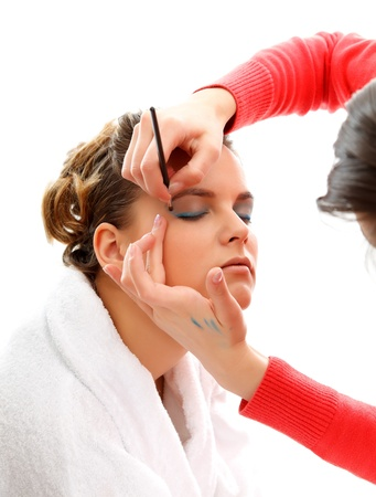 Cosmetician doing makeup to a young model photo