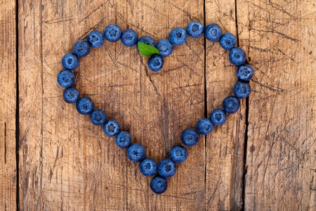 sweet love: Shape of heart made of blueberries on wooden table
