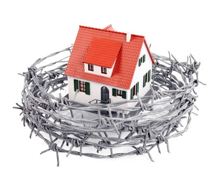 metal wire: Protection of a miniature house with a barbed wire, concept Stock Photo