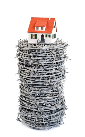 Miniature house with barbed wire, concept Stock Photo - 10726668