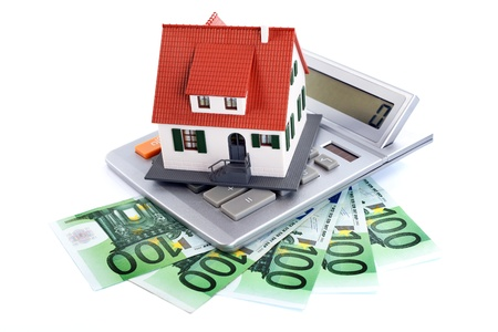 Miniature house with money and counter, new home concept Stock Photo
