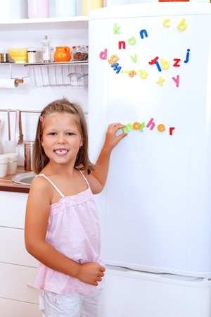 refrigerador: Chica con imanes de nevera de letras en la cocina Foto de archivo
