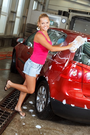 Pretty young woman washing her car photo