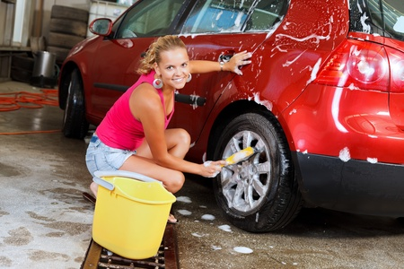 Sexy young woman washing the wheels of her car
