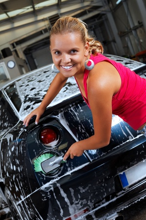 Sexy blonde cleans the rear lights of a sport car Stock Photo - 10845349