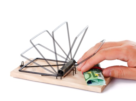Hand taking money from the wooden mousetrap Stock Photo - 10997820