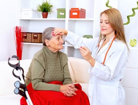 Young nurse checking body temperature for a senior woman
