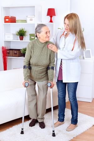 aide a domicile: Infirmi�re soignant dame �g�e avec des b�quilles