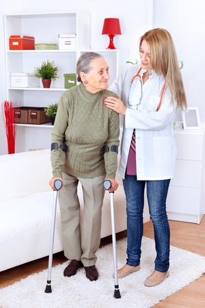 home care nurse: Nurse helping senior lady with crutches