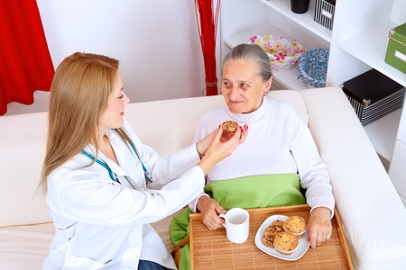 Lovely nurse helping old woman eating cookies Stock Photo