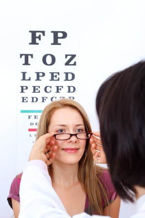 Optician helps woman to choose the best pair of glasses photo