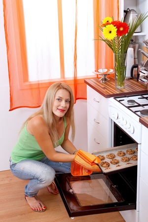 Pretty woman taking the cookies out of the oven Stock Photo - 11321510