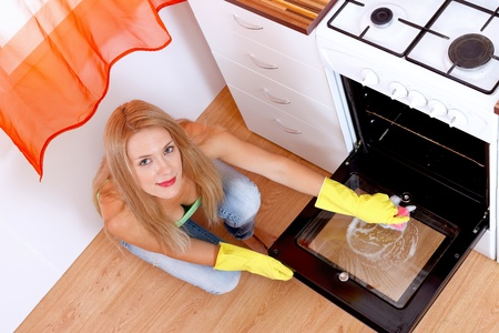 Lovely woman wearing yellow gloves cleaning the dirty oven  photo