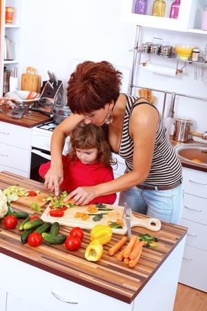 Mother helping daughter making salad photo