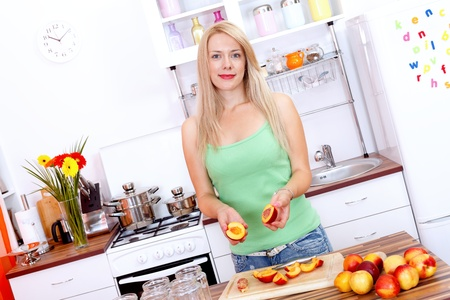 Woman making canned peaches in the kitchen Stock Photo - 11321483