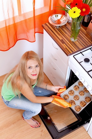 Young woman taking cookies out of oven Stock Photo - 11321514