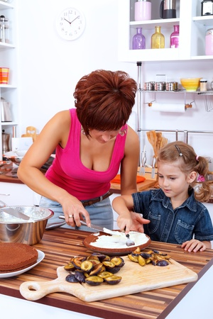 Mother and daughter making a cake with damson plums in the kitchen photo