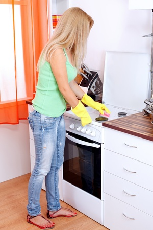 Young woman with yellow gloves cleaning the oven Stock Photo - 11321501