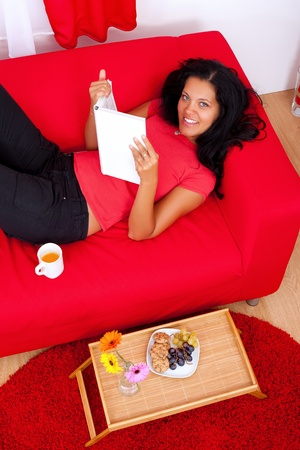 Young woman lying on the sofa reading a book  photo