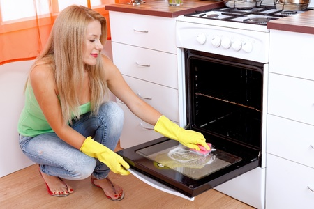 Young woman cleaning the oven with a sponge in the kitchen Stock Photo - 11321507
