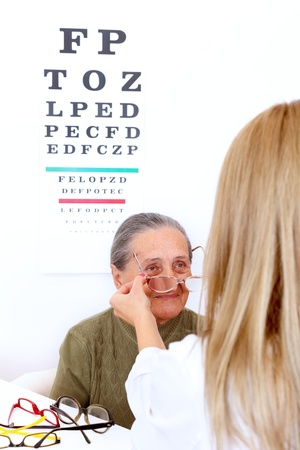 Elderly woman choosing a pair of glasses at the optician photo