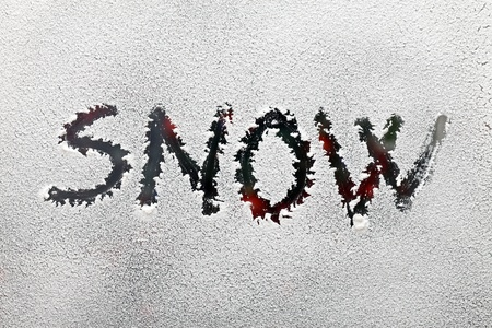 Snow written on the glass with snow, red ornaments in the background photo