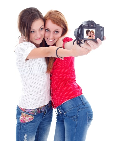 Two lovely young girls with camera taking photo about themselves photo