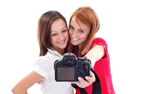 Smiling young girls taking photo about themselves using a camera photo