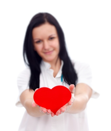 Nurse offering a red paper heart to us over white background photo