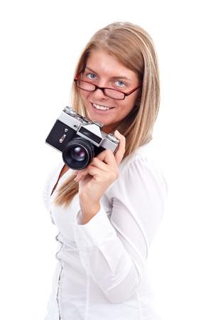 Sonriente mujer joven con la cámara de estilo antiguo en la mano, fondo blanco