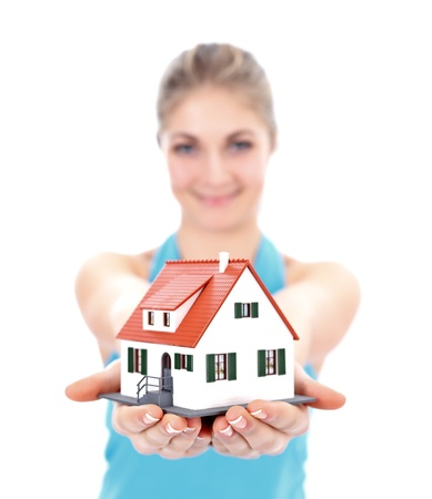 Pretty girl offering a miniature house for us Stock Photo - 12175953