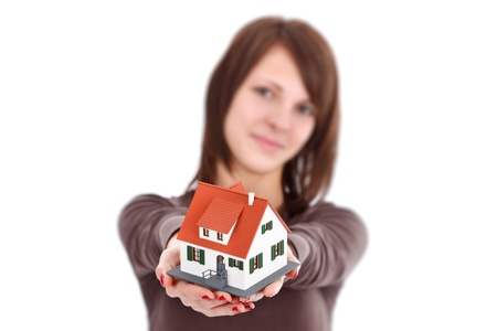 Lovely woman offering a miniature house, symbol of a new home Stock Photo - 12176177