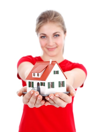 Girl offering a miniature house for us, concept Stock Photo - 12176161