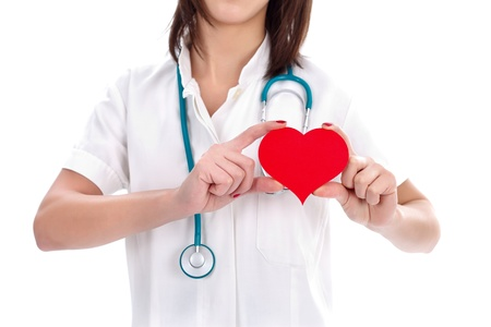Nurse holding a red paper heart showing the place of it photo