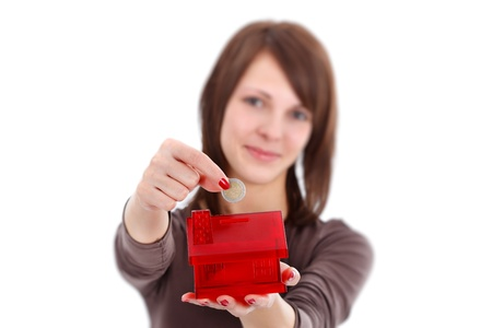 money box: Woman putting coins in money box with form of a house