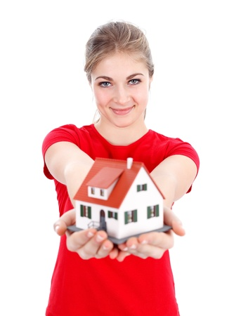 Smiling girl offering us a miniature house, new home concept Stock Photo - 12176089