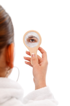 Young model with beauty mask on her face looks in the mirror Stock Photo - 12891479