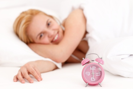 Girl lying in bed, before her an alarm clock Stock Photo - 12891400