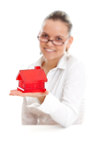 Smiling woman offering a red house to us