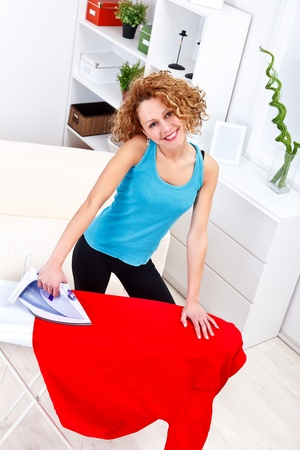 Happy housewife ironing at home  photo