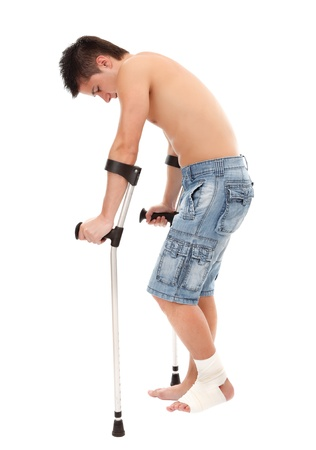 Young man walks with crutches, isolated on white background