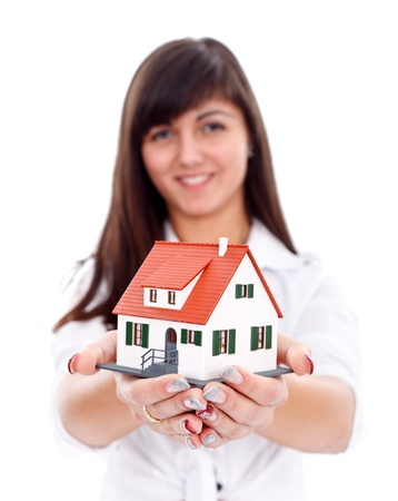 Young brunette with a miniature house, new home concept