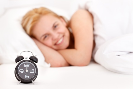 Woman waking up, alarm clock in front   photo