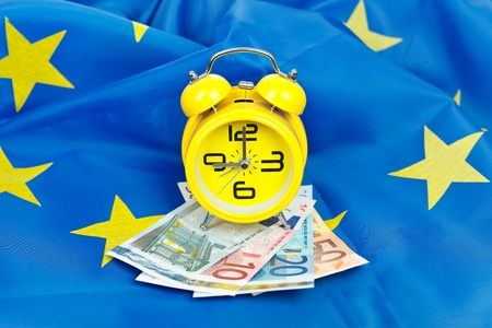 EU flag with euros and alarm clock, concept
