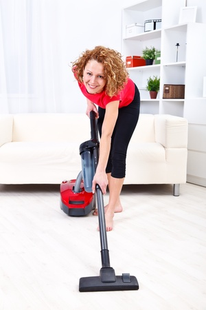 Pretty young woman using vacuum cleaner at home Stock Photo - 12904721