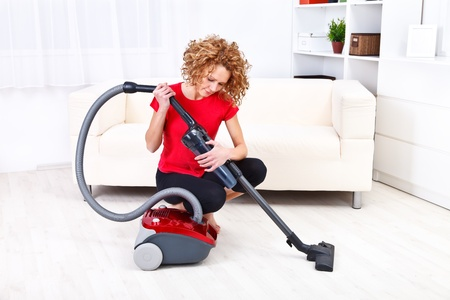 vacuum: Pretty young woman repairing vacuum cleaner at home