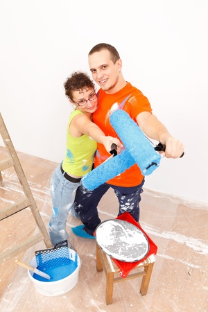 Happy young couple with roller brush near the ladder  photo